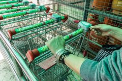 Woman inserts coin to supermarket trolley stock photography