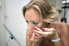 Woman, inserts a contact lens. In an eye Royalty Free Stock Photography