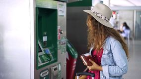 Young woman charging travel pass on station. Woman inside big terminal or train station charging travel pass on modern machine and go away stock footage