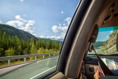 Young tourist woman. Woman inside the car driving and show map on the country roadway between fields with brown grass and snowy mountains . Sun is shining. Shoot royalty free stock photography
