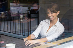 Woman inside coffee shop working on laptop Stock Photography