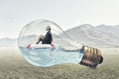 Woman inside light bulb. Young businesswoman floating on life buoy inside of light bulb Royalty Free Stock Images