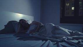 Woman with insomnia lying in bed with open eyes. At night stock video footage