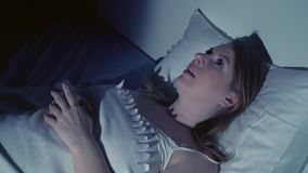 Woman with insomnia lying in bed with open eyes. At night stock footage