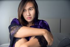 Woman from insomnia. Portrait of a young woman in purple satin nightwear suffering from insomnia Stock Photo