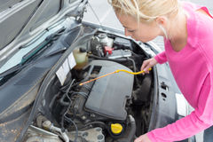 Woman inspecting broken car engine. Stock Image