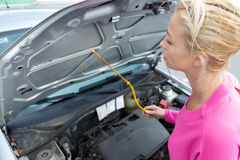 Woman inspecting broken car engine. Royalty Free Stock Photography