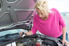 Woman inspecting broken car engine. Royalty Free Stock Photo