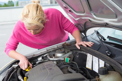 Woman inspecting broken car engine. Royalty Free Stock Photos