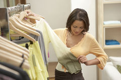 Woman Inspecting Clothes Stock Image