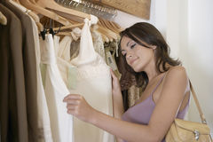 Woman Inspecting Dress Stock Images