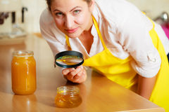 Woman inspecting honey with magnifying glass. Royalty Free Stock Image