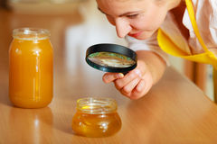 Woman inspecting honey with magnifying glass. Royalty Free Stock Images