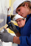 Woman installing an electrical outlet. Young women installing an electrical outlet stock image