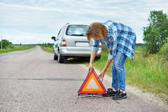 Woman installing emergency sign on road near car Stock Images