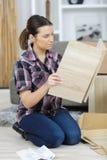 Woman installing laminate flooring in room. Woman installing laminate flooring in the room Stock Photo