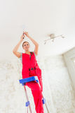 Woman Installing light fitting Stock Images