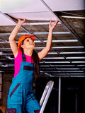 Woman installing suspended ceiling Stock Photography