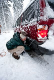 Woman installing tire chains Stock Photography