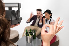 Woman with instant camera photographing happy young couple drinking beer together Stock Photo