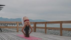 Female yoga trainer is showing positions, standing outside near seacoast stock footage