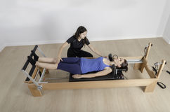 Woman and instructor in reformer bed, pilates. Woman doing exercise of pilates with instructor in reformer bed stock photos