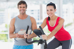 Woman with instructor working out at spinning class in bright gym Royalty Free Stock Images