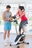 Woman with instructor working out at spinning class Stock Image