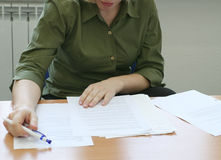 Woman intently reading the documents (front). Woman in the office intently reading the documents Royalty Free Stock Images