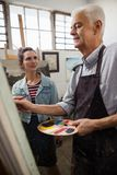 Woman interacting while senior man painting on canvas. Woman interacting while senior men painting on canvas in drawing class stock images