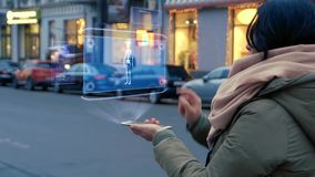 Woman interacts HUD hologram with skeleton. Unrecognizable woman standing on the street interacts HUD hologram with skeleton. Girl in warm clothes with a scarf stock video
