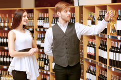 Woman interacts with a sommelier in shop Stock Photography