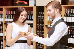 Woman interacts with a sommelier in shop Stock Photos