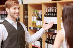 Woman interacts with a sommelier in shop. Excellent choice. Close-up of a salesman giving young women advice on buying bottle of wine Stock Images
