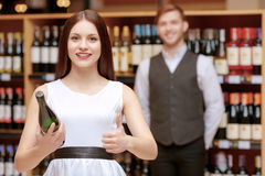 Woman interacts with a sommelier in shop. Great service. Young smiling brunette women holding a wine bottle and giving thumbs up to salesman in liquor store Royalty Free Stock Photos