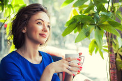 Woman in interior holfing a cup of coffe in hands Royalty Free Stock Photo
