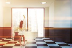 Woman in white gray bathroom with tub royalty free stock images