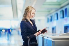 Woman in international airport at check-in counter, giving her passport to an officer Royalty Free Stock Photo