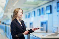 Woman in international airport at check-in counter, giving her passport to an officer Stock Photos