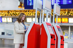 Woman at international airport, checking in on electronic termin Stock Images