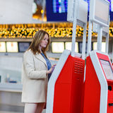 Woman at international airport, checking in on electronic termin Royalty Free Stock Photo