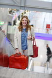Woman at international airport, on escalator at arrival terminal Royalty Free Stock Image