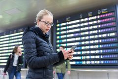 Woman in international airport checking flight information on smart phone app. Royalty Free Stock Image