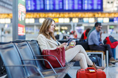 Woman at international airport, reading ebook and drinking coffe. Young woman at international airport, reading her ebook computer and drinking coffee to go Stock Photo