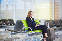 Woman in international airport terminal, working on her laptop. Young elegant business woman with hand luggage in international airport terminal, working on her Royalty Free Stock Photo