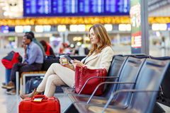 Woman at international airport waiting for flight. Business woman at international airport reading book and drinking coffee in terminal. Angry passenger waiting Stock Images