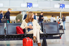 Woman at international airport waiting for flight Stock Photo
