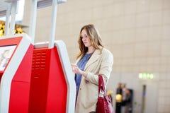 Woman at international airport waiting for flight Royalty Free Stock Photo