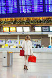Woman at international airport waiting for flight Royalty Free Stock Image