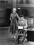 Woman interrupting man at typewriter Royalty Free Stock Images
